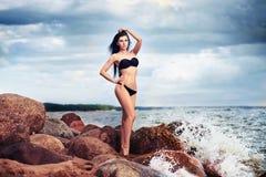 黑比基尼泳装的美丽的亭亭玉立的妇女 海滩、沙子和石头 免版税库存照片