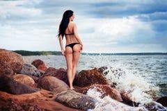 黑比基尼泳装的美丽的亭亭玉立的妇女 海滩、沙子和石头 库存照片