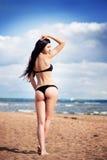 黑比基尼泳装的美丽的亭亭玉立的妇女 海滩,沙子蓝天 免版税图库摄影