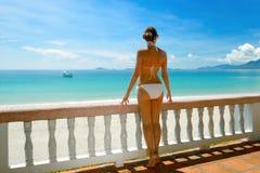 比基尼泳装的美丽的妇女在大阳台敬佩海的。 免版税库存照片