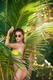 比基尼泳装的美丽的妇女在热带棕榈下 背景复制绿色空间 库存图片