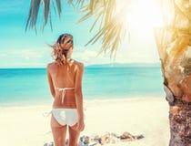 比基尼泳装的美丽的妇女在热带海滩wih棕榈树白色 免版税库存图片