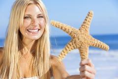 比基尼泳装的美丽的妇女女孩有在海滩的海星的 免版税库存图片