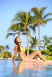 比基尼泳装的美丽的妇女晒日光浴在旅行的 库存图片