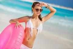 比基尼泳装的美丽的妇女有lifebuoy的桃红色的 免版税库存照片