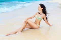 比基尼泳装的美丽的少妇在一个热带海滩 免版税库存照片