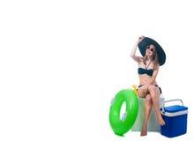比基尼泳装的美丽的少妇在一个更加凉快的袋子坐 免版税库存照片