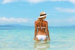 比基尼泳装的美丽的少妇在晴朗的热带海滩   免版税库存照片