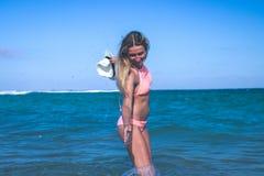 比基尼泳装的美丽的少妇在飞溅水的海滩 热带海岛巴厘岛,印度尼西亚 免版税库存图片