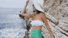 比基尼泳装的美丽的少妇有大帽子和太阳镜的在海滩松弛近的岩石在海背景 布德瓦 股票视频