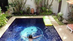 比基尼泳装的美丽的年轻女人进入游泳场游泳,并且寄生虫飞行在热带海岛上的豪华别墅 股票录像