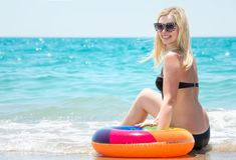 比基尼泳装的美丽的性感的妇女有可膨胀的圈子的坐海滩 免版税库存图片