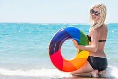 比基尼泳装的美丽的性感的妇女有可膨胀的圈子的坐海滩 库存照片