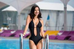黑比基尼泳装的美丽的愉快的女性有在游泳池附近的匀称身体的在手段 库存图片