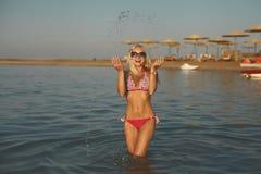 比基尼泳装的美丽的时兴和性感的运动的白肤金发的女孩有乐趣时间在海 免版税库存照片