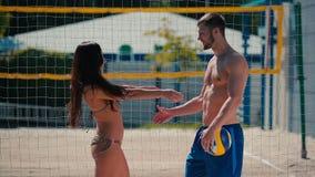 比基尼泳装的美丽的浅黑肤色的男人与人回面简而言之在排球` s网附近的 影视素材