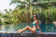 比基尼泳装的美女坐游泳池边 免版税库存图片