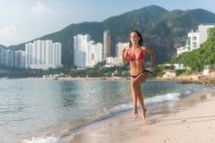 比基尼泳装的适合的少妇有跑步在海滨的运动的肌肉性感的身体的反对山和高大厦 免版税库存图片