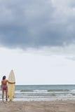 比基尼泳装的镇静妇女有在海滩的冲浪板的 图库摄影