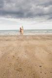 比基尼泳装的镇静妇女有在海滩的冲浪板的 免版税库存图片