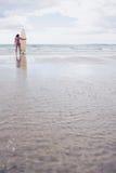 比基尼泳装的镇静妇女有在海滩的冲浪板的 库存图片