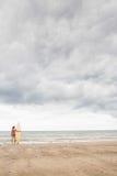 比基尼泳装的镇静妇女有在海滩的冲浪板的 免版税图库摄影