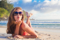 比基尼泳装的长发女孩在热带塞舌尔群岛海滩吹的空气亲吻 免版税图库摄影