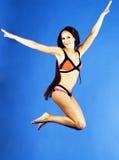 比基尼泳装的年轻俏丽的微笑的愉快的亭亭玉立的跳跃的女孩在蓝色背景,假期概念关闭的生活方式人  库存照片