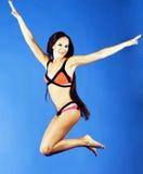 比基尼泳装的年轻俏丽的微笑的愉快的亭亭玉立的跳跃的女孩在蓝色背景,假期概念关闭的生活方式人  免版税库存图片
