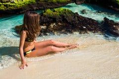 比基尼泳装的年轻时尚妇女坐热带海滩 Beautif 免版税库存照片