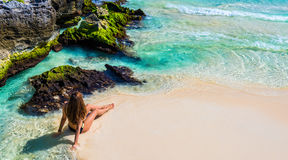 比基尼泳装的年轻时尚妇女坐热带海滩 Beautif 库存照片
