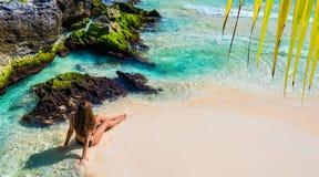 比基尼泳装的年轻时尚妇女坐热带海滩 Beautif 免版税库存图片