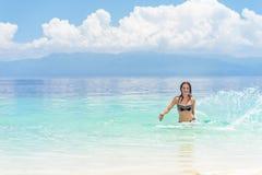 比基尼泳装的年轻欧洲妇女充满飞溅和跳舞在美丽的热带风平浪静的好心情在多云软的天空下 图库摄影