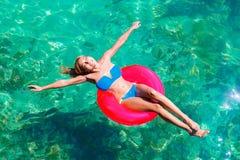 比基尼泳装的年轻美丽的女孩在rubb的热带海游泳 图库摄影