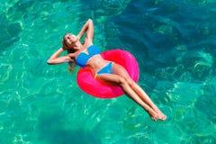 比基尼泳装的年轻美丽的女孩在rubb的热带海游泳 库存图片