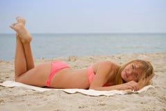 比基尼泳装的年轻美丽的女孩晒日光浴在海滩的 库存图片