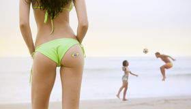 比基尼泳装的年轻美丽的妇女在使用与橄榄球的海滩观看的夫妇 库存图片