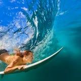 比基尼泳装的活跃女孩在对水橇板的下潜行动 免版税图库摄影