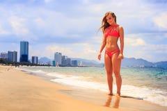 比基尼泳装立场的白肤金发的亭亭玉立的体操运动员在海边缘微笑  免版税库存照片