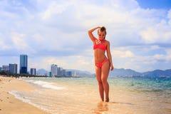 比基尼泳装立场的白肤金发的亭亭玉立的体操运动员在海边缘接触头发 库存图片