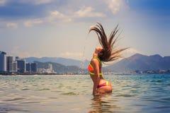 比基尼泳装立场的白肤金发的女孩在海摇的头提起头发 免版税库存图片