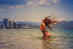 比基尼泳装立场的白肤金发的女孩在海摇的头提起头发 库存照片