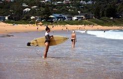 比基尼泳装等待的波浪的美丽的冲浪者妇女 免版税图库摄影