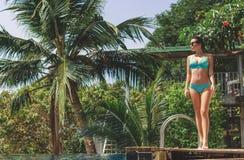比基尼泳装身分的美女在游泳场附近 免版税库存图片