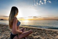 比基尼泳装选址的可爱的性感的妇女在偏僻的海滩的沙子 库存图片