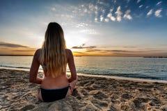 比基尼泳装选址的可爱的性感的妇女在偏僻的海滩的沙子 库存照片