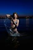 比基尼泳装飞溅的年轻美丽的性感的妇女在外面 免版税库存照片