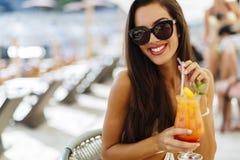 比基尼泳装饮用的鸡尾酒的笑的妇女 免版税库存照片