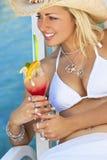 比基尼泳装饮用的鸡尾酒的美丽的少妇由海 免版税库存图片