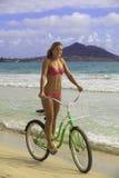 比基尼泳装骑马的白肤金发的女孩她的自行车 库存照片